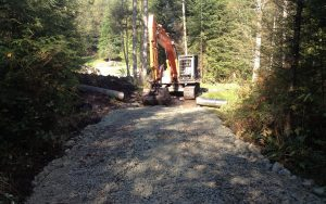 excavator smoothing gravel on an access road