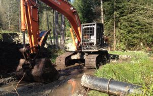excavator prepping for drainage on a access road build