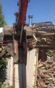 close up view excavator house demolition