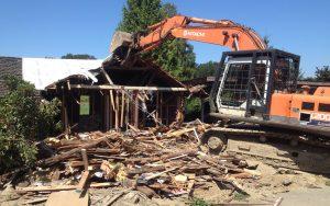 large excavator demo on house